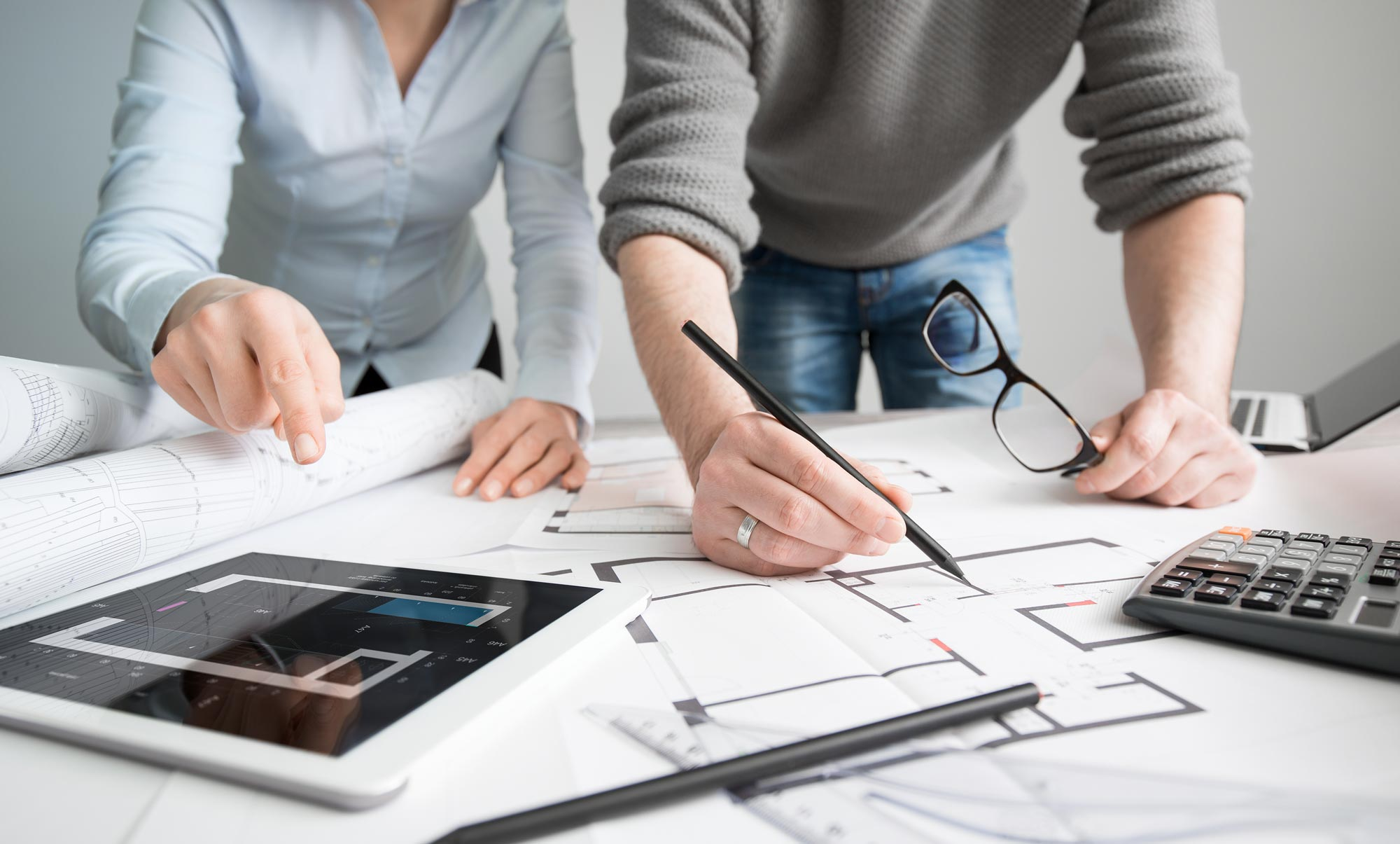 two people leaning over the plan of the kitchen